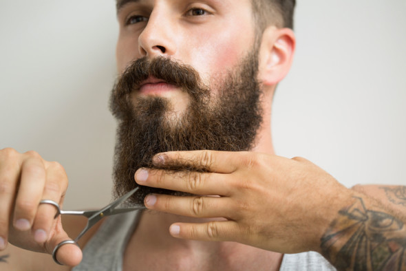 Close up of man trimming beard with scissors