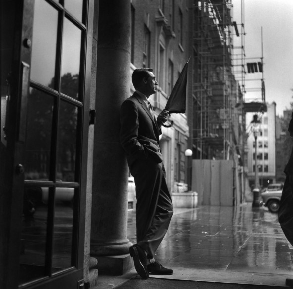 British-born American actor Cary Grant (1904 - 1986) sheltering in a hotel porch as he waits for the rain to stop. (Photo by Express/Getty Images)