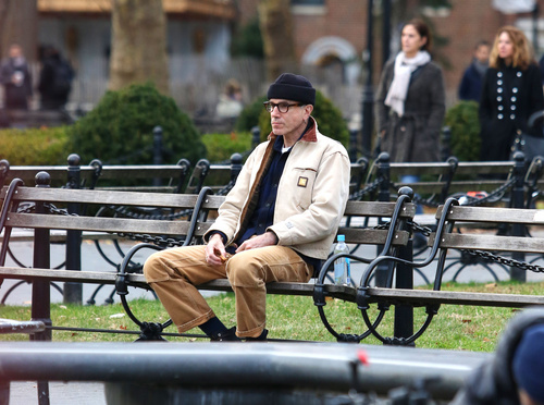 Retired actor Daniel Day-Lewis sits alone at a park bench and goes unnoticed by pedestrians in New York City.